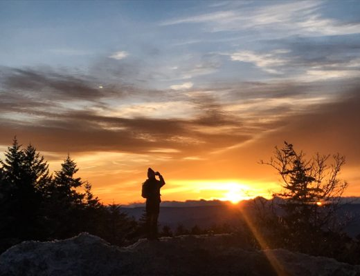 Girl photographing sunset in mountains