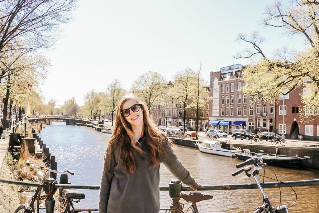 Girl in front of canal bridge in Amsterdam
