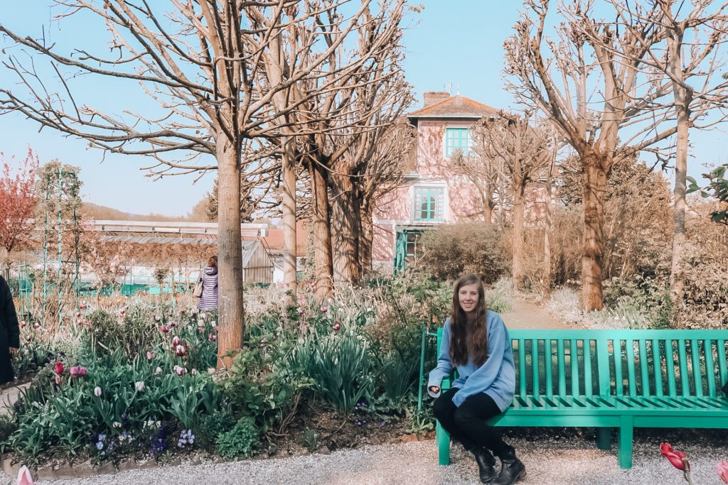 Girl sitting on bench in gardens at Giverny
