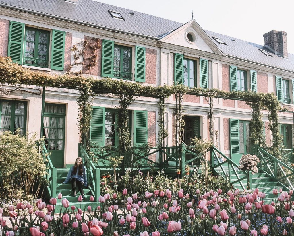 Girl in front of pink Giverny house